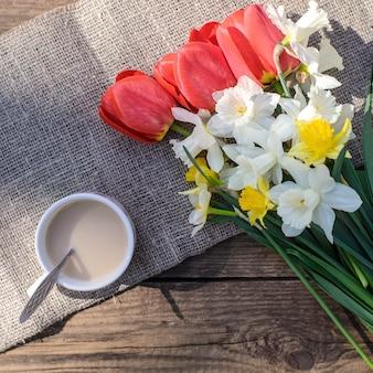 Piękny bukiet wiosennych białych kwiatów żonkili, czerwonych tulipanów i filiżanki kawy z mlekiem na drewnianej powierzchni