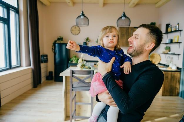 Piękny caucasian mężczyzna bawić się z małą córką w wewnętrznym studiu