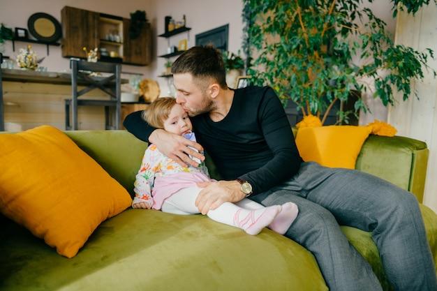 Piękny caucasian mężczyzna dba o jego małej ślicznej córki na leżance