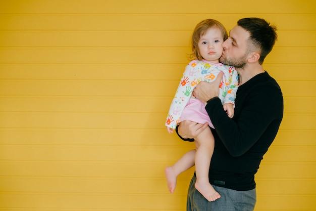 Piękny caucasian mężczyzna trzyma w ręce jego małej córki nad kolor żółty ścianą