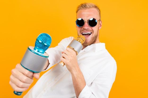 Piękny caucasian mężczyzna w szkłach śpiewa piosenki w karaoke z mikrofonem odizolowywającym na kolorze żółtym