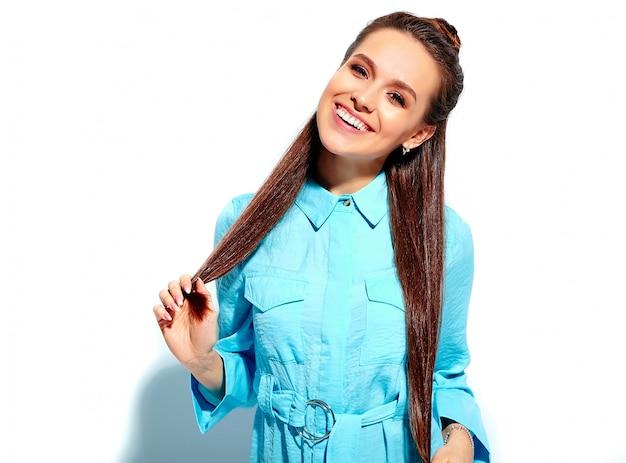 Piękny caucasian uśmiechnięty brunetki kobiety model w jaskrawego błękitnego lata eleganckiej sukni odizolowywającej na białym tle