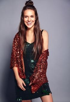 Piękny caucasian uśmiechnięty modniś brunetki kobiety model w jaskrawym goleniu odbija lato stylową kurtkę i zieleni suknię pozuje na szarość