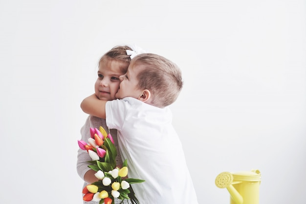 Piękny chłopak i dziewczyna z tulipanów z uściskiem. dzień matki, 8 marca, wszystkiego najlepszego