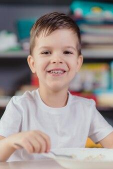 Piękny chłopak je owsiankę mleczną. śliczny dziecko ma śniadaniowego obsiadanie przy stołem w kuchni w domu.