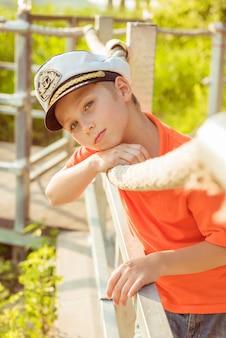 Piękny chłopak opowiada o sznurze w czapce kapitana