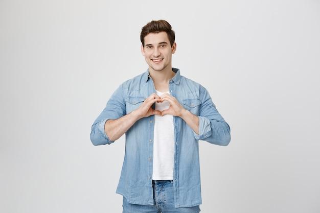 Piękny chłopak pokazuje gest serca i uśmiecha się