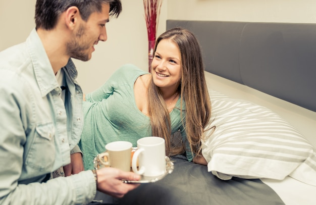 Piękny chłopak przynosi śniadanie swojej dziewczynie rano
