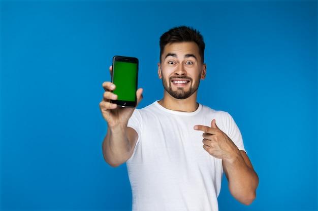 Piękny chłopak uśmiecha się i pokazuje coś na telefon w aparacie