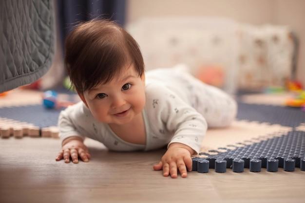 Piękny chłopczyk z ciemnymi włosami w jasnej piżamie uczący się czołgać i leżeć na brzuchu na podłodze w pokoju dziecinnym