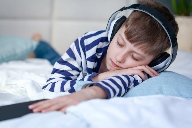Piękny chłopiec dziecko leży na łóżku i słucha muzyki lub podcastu