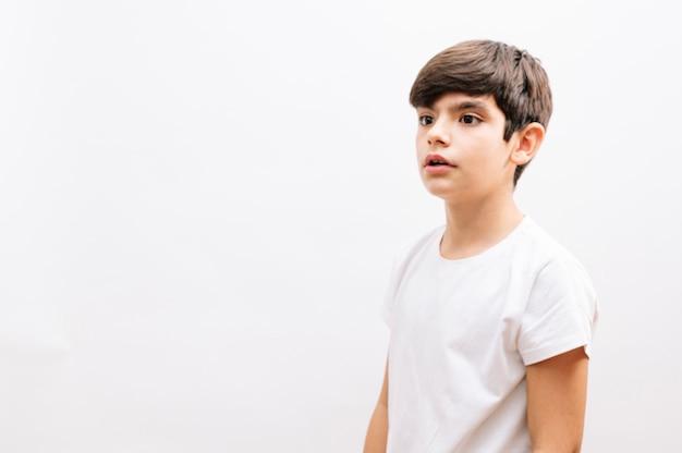 Piękny chłopiec dziecko na sobie dorywczo t-shirt stojący na białym tle patrząc z boku.