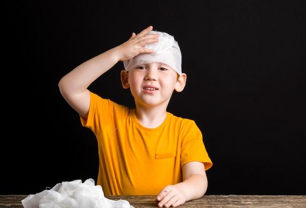 Piękny chłopiec z rudymi włosami z uszkodzoną głową bandażuje się bandażem medycznym, chłopiec ze sprzętem medycznym podczas samodzielnego leczenia