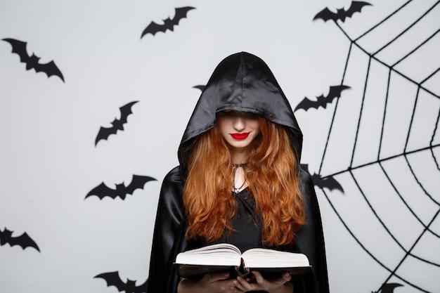 Piękny ciemny ksiądz rzucony czary z magii książką na popielatym tle.