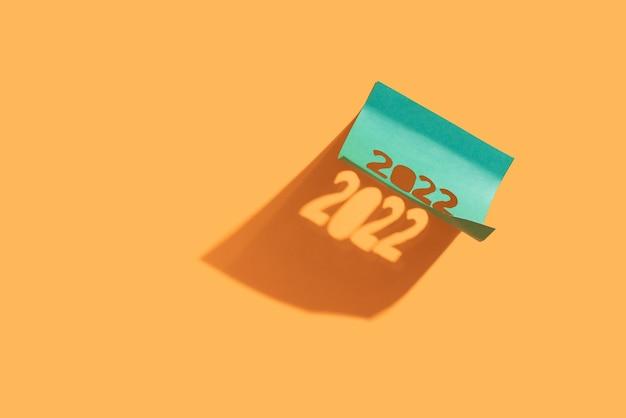 Piękny cień z wklejonego papieru firmowego z wyciętymi numerami 2022, na żółtym tle, koncepcja noworoczna, zbliżenie.