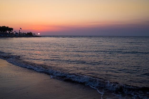 Piękny cloudscape nad morzem, zmierzchu strzał. majestatyczny zmierzch nad dennym brzeg. romantyczny wieczór na plaży. wolność i inspiracja nad oceanem. fale na plaży o zachodzie słońca, światło słoneczne odbija