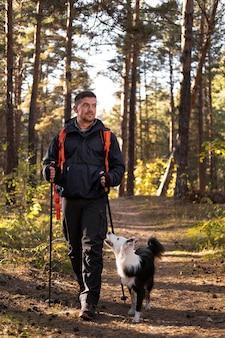 Piękny czarno-biały pies i chodzący mężczyzna