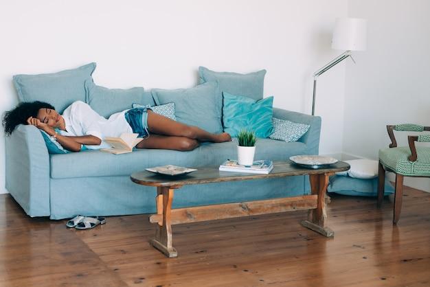Piękny czarny młodej kobiety dosypianie w kanapie