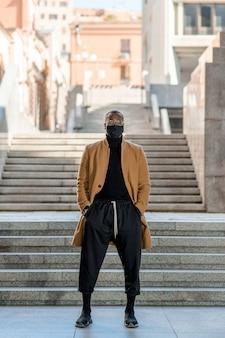 Piękny czarny model pozowanie w mieście. człowiek stojący z rękami w kieszeni patrząc na kamery ze schodami na tle.