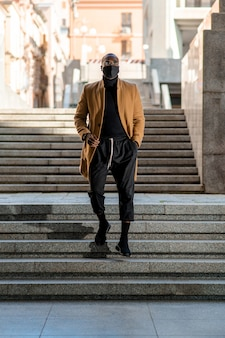 Piękny czarny model pozowanie w mieście. człowiek z rękami w kieszeni schodzi na dół.