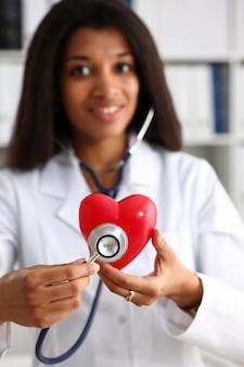 Piękny czarny uśmiechnięty kobiety lekarki chwyt
