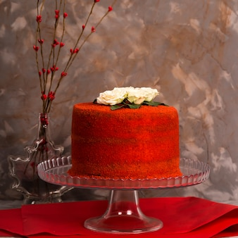 Piękny czerwony aksamitny tort ozdobiony białymi różami