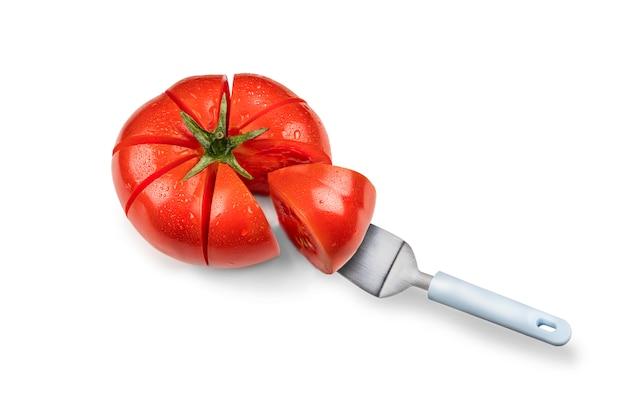 Piękny czerwony pomidor, pokrojony na kawałki jak ciasto. kawałek łopatki do ciasta. zdrowe jedzenie wegetariańskie. odosobniony