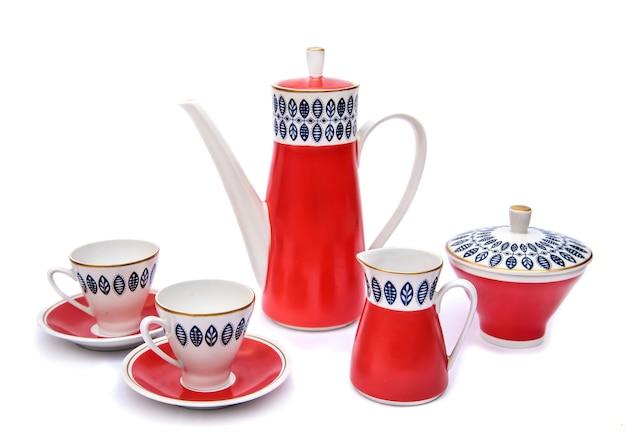 Piękny czerwony porcelanowy serwis do kawy dzbanek do kawy, filiżanki, dzbanek ze śmietaną i cukiernica izolują na białym tle