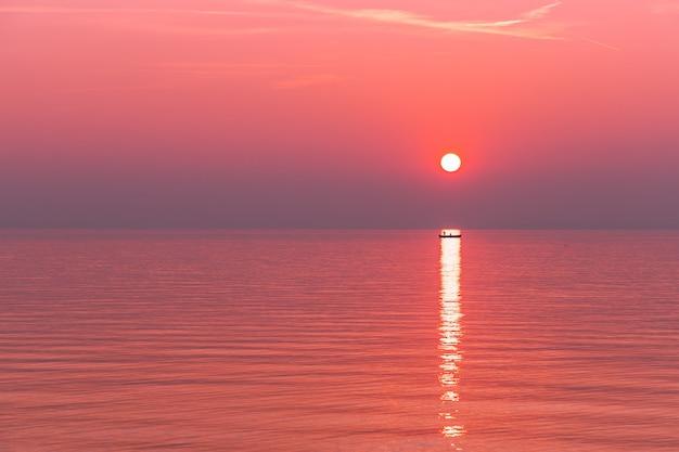 Piękny czerwony zachód słońca we mgle nad jeziorem garda. w promieniach zachodzącego słońca widać sylwetkę łodzi z rybakami.
