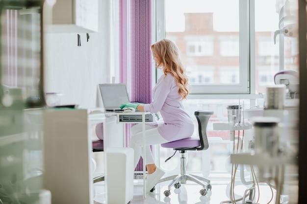 Piękny dentysta z długimi kręconymi włosami w fioletowym mundurze pracuje na białym laptopie w gabinecie