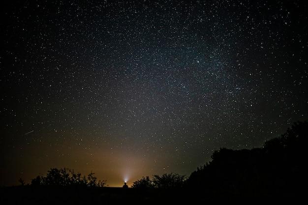 Piękny długi strzał mężczyzna siedzi pod niebem