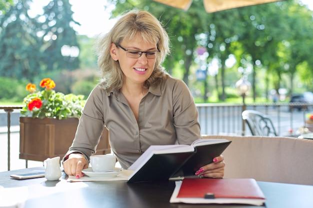 Piękny dojrzały biznes kobieta pije kawę przy przerwie w restauracji na świeżym powietrzu, uśmiechnięta blondynka w okularach, szara koszula