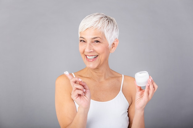 Piękny dojrzały kobiety mienia słój skóry śmietanka dla twarzy i ciała odizolowywających na szarym tle. szczęśliwa starsza kobieta stosuje starzenie się moisturizer i patrzeje kamerę. zabieg przeciwstarzeniowy beauty.