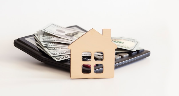 Piękny dom stojący na 100 dolarowych banknotach na kalkulatorze