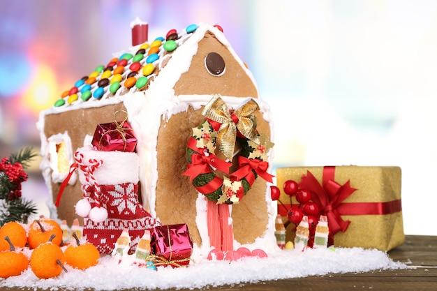 Piękny domek z piernika ze świątecznym wystrojem na drewnianym stole