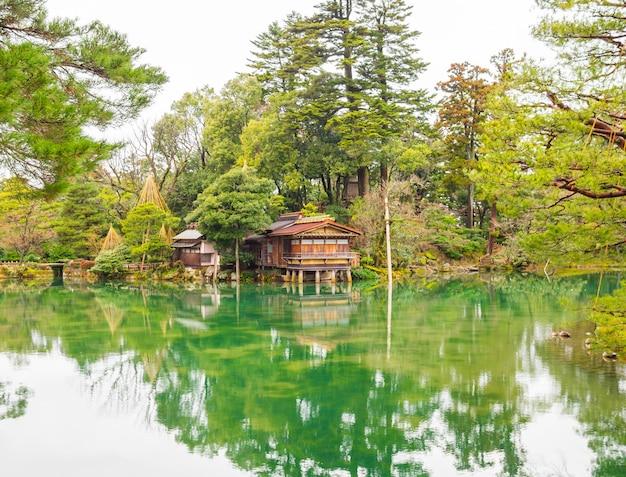 Piękny drewniany dom na skraju stawu w zacienionym ogrodzie w stylu japońskim.