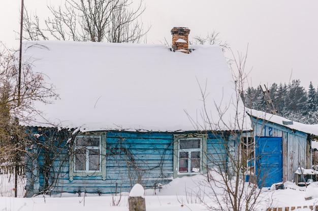 Piękny drewniany dom pokryty świeżym śniegiem. bezludna stara zimowa przytulna chata w pustej wiosce