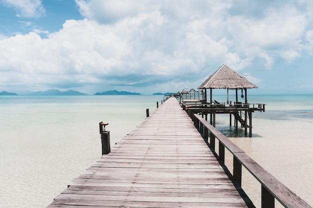 Piękny drewniany most nad morzem na niebieskim niebie. i biała chmura.