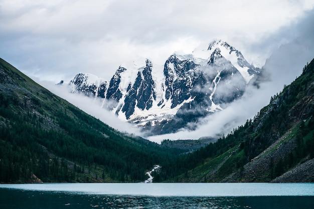 Piękny duży lodowiec, skaliste zaśnieżone góry, las iglasty na wzgórzach, górskie jezioro i górska potok pod zachmurzonym niebem.