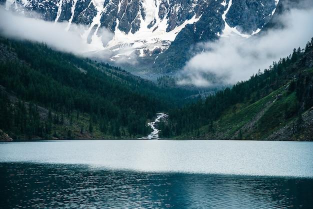 Piękny duży lodowiec, skaliste zaśnieżone góry wśród niskich chmur, las iglasty na wzgórzach, górskie jezioro i góralska potok