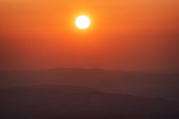 Piękny duży zachód słońca nad morzem. spokojna scena zbliżenie czerwonego słońca i czerwonego nieba słońca.