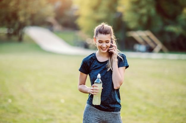 Piękny dysponowany uśmiechnięty kaukaski kobieta w odzieży sportowej i kucyk stojący w przyrodzie, rozmawia przez telefon i trzymając butelkę z orzeźwieniem. fitness w koncepcji natury.