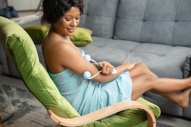Piękny dzień. afro-kobieta w ręcznik robi swoje codzienne zabiegi pielęgnacyjne w domu. siedząc na sofie, masując skórę ramion, uśmiechając się. pojęcie piękna, samoopieki, kosmetyki, zdrowego stylu życia.