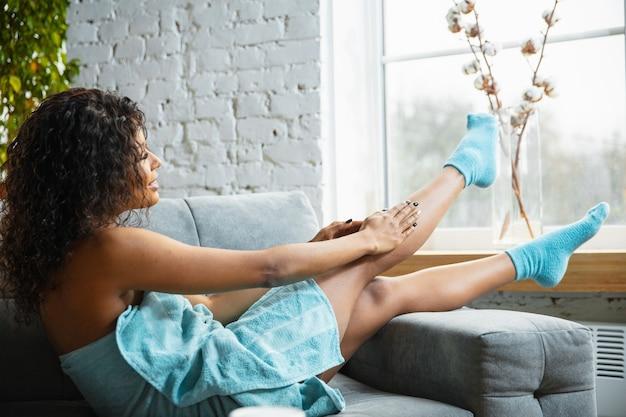 Piękny dzień. afroamerykanka w ręczniku robi codzienną pielęgnację skóry w domu. siedząc na kanapie, masując, nakładając krem nawilżający na skórę nóg. pojęcie piękna, samoopieki, kosmetyki, młodości.