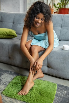 Piękny dzień. afroamerykanka w ręczniku robi codzienną pielęgnację skóry w domu. siedzenie na sofie, masowanie, nakładanie kremu nawilżającego na skórę nóg.
