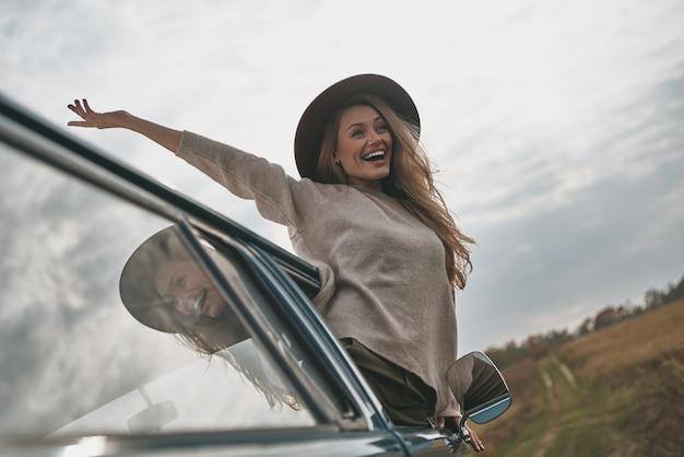 Piękny dzień. atrakcyjna młoda uśmiechnięta kobieta wychylająca się przez okno furgonetki i trzymająca wyciągnięte ręce podczas jazdy samochodem