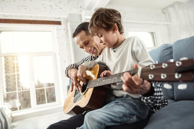 Piękny dzień. atrakcyjna zawartość jasnowłosy chłopak uczy się gry na gitarze siedząc na kanapie i uśmiechnięty ojciec