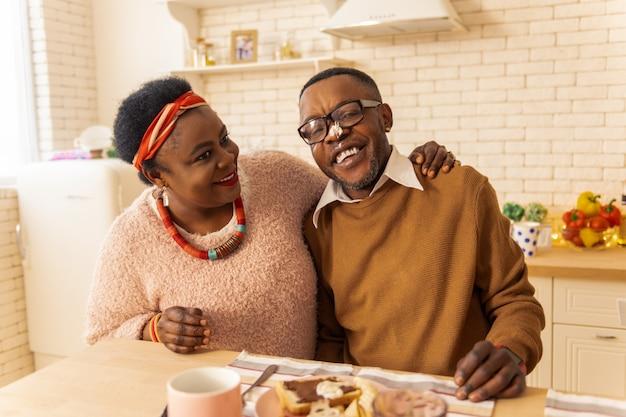 Piękny dzień. miły, radosny mężczyzna w pozytywnym nastroju jedząc śniadanie ze swoją dziewczyną