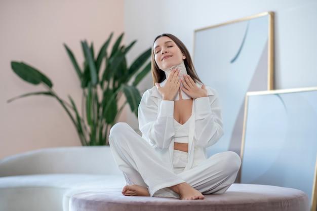 Piękny dzień. młoda kobieta w bieli siedzi na okrągłym krześle z taśmami na szyi