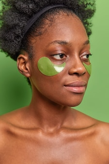 Piękny dzień. poważna modelka nakłada hydrożelowe plastry pod oczy, aby nawilżyć skórę, ma pewny wygląd pozuje bez koszulki na zieloną ścianę, stara się zmniejszyć zmarszczki